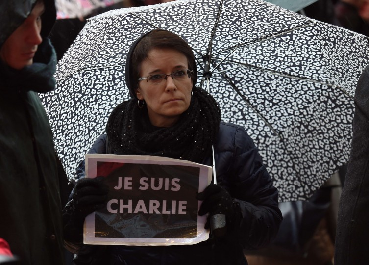 "A woman with an umbrella holds a sign reading ""Je suis Charlie"" (I am Charlie) as European Parliament members hold a minute of silence at the European Parliament in Brussels on January 8, 2015, for the victims of the January 7 attack against French satirical weekly newspaper Charlie Hebdo which left 12 people dead. A stunned and outraged France began a national day of mourning on January 8, as security forces desperately hunted two brothers suspected of gunning down 12 people in an Islamist assault on a satirical weekly, the country's bloodiest attack in half a century. Emmanuel Duand/AFP/Getty Images"