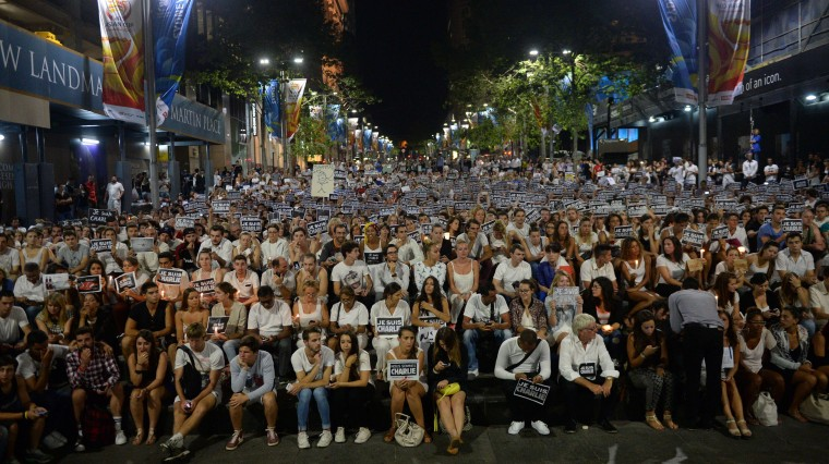 """Members of Sydney's French community gather in the heart of the city to hold aloft banners reading """"Je Suis Charlie"""" (I am Charlie) on January 8, 2015, in tribute to the victims killed after gunmen opened fire in the offices of French satirical weekly Charlie Hebdo in Paris the day before. The vigil, just metres from where two hostages and a gunman died after a cafe siege in Sydney's Martin Place less than a month ago, saw many French and Australians carrying white and black """"Je Suis Charlie"""" placards. Peter Parks/AFP/Getty Images"""