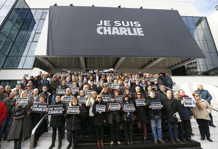 "People pose holding signs reading ""Je suis Charlie"" outside the Palais des Festivals in Cannes where a banner reading the same message has been deployed as a tribute to the satirical weekly Charlie Hebdo on January 9, 2015. January 7 drama unfolded almost 48 hours into a massive manhunt launched after the brothers burst into the office of the satirical weekly Charlie Hebdo and gunned down staff members and two policemen, saying they were taking revenge for the magazine's publication of cartoons offensive to many Muslims. The number of people seized was not immediately confirmed. Valery Hache/AFP/Getty Images"
