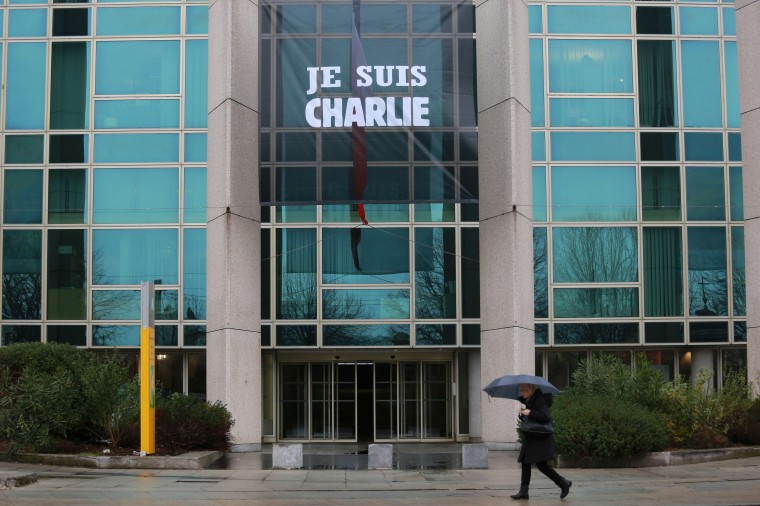 "A woman walks past a banner reading ""Je suis Charlie"" (I am Charlie) displayed next to a French flag flying half-mast on the building of the Conseil regional (regional council) of Aquitaine in Bordeaux, southwestern France, on January 9, 2015, following an attack by gunmen on the offices of the satirical weekly Charlie Hebdo on January 7 which left 12 dead. Nicholas Tucat/AFP/Getty Images"