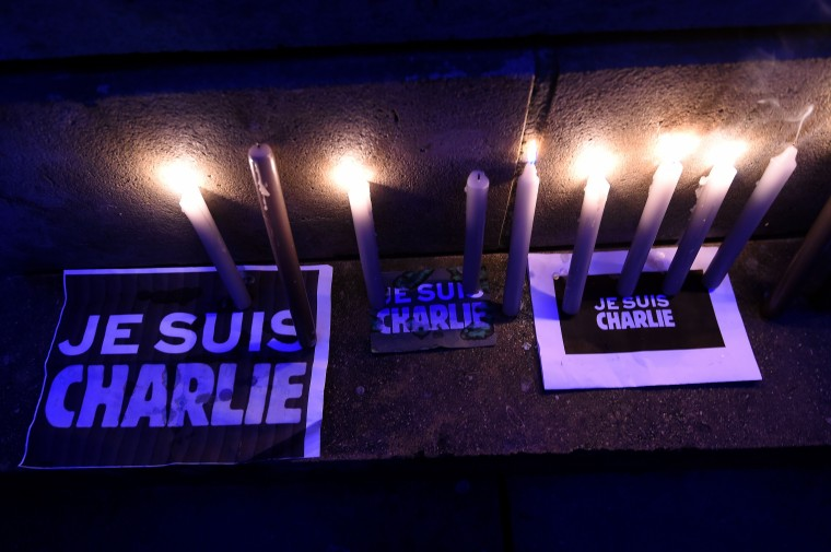 "Candles are lit on signs reading ""Je suis Charlie"" (I am Charlie) during a gathering in Brussels on January 9, 2015 to pay tribute to the victims of a deadly attack on the Paris headquarters of French weekly Charlie Hebdo. Elite commandos units killed the two suspects in the Charlie Hebdo massacre during a simultaneous assault on the building they were holed up in and on a Paris Jewish supermarket, freeing hostages at both sites. Emmanuel Duande/AFP/Getty Images"