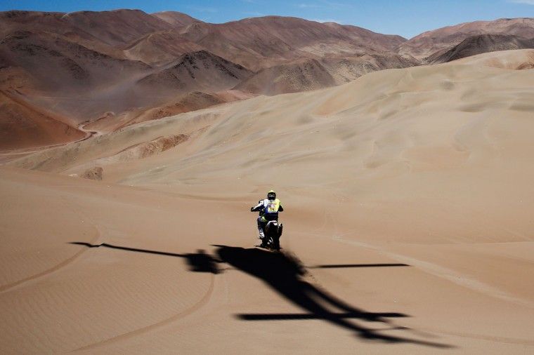 #14 Alain Duclos of France riding for Sherco TVS Rally Factory RTR450 competes with the shadow of the TV helicopter following him during day 6 of the Dakar Rally between Antofaasta and Iquique on January 9, 2015 near Iquique, Chile. (Photo by Dean Mouhtaropoulos/Getty Images)