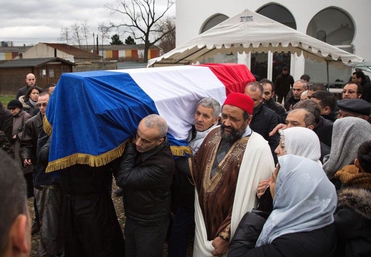 A coffin containing the body of a murdered police officer is carried during a funeral at a muslim cemetary on January 13, 2015 in Bobigny, France. The officers were awarded a posthumous Legion dHonneur, inrecognition of their bravery. The terrorist attacks began on Wednesday with the assault on the French satirical magazine Charlie Hebdo, killing 12, and ended on Friday with sieges at a printing company in Dammartin en Goele and a Kosher supermarket in Paris with four hostages and three suspects being killed. A fourth suspect, Hayat Boumeddiene, 26, escaped and is wanted in connection with the murder of a policewoman. (Photo by Dan Kitwood/Getty Images)