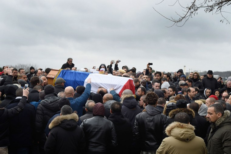 The coffin of policie officer Ahmed Merabet, draped in the French flag, is carried during a funeral at a muslim cemetary on January 13, 2015 in Bobigny, France. The officers were awarded a posthumous Legion dHonneur, in recognition of their bravery. The terrorist attacks began on Wednesday with the assault on the French satirical magazine Charlie Hebdo, killing 12, and ended on Friday with sieges at a printing company in Dammartin en Goele and a Kosher supermarket in Paris with four hostages and three suspects being killed. A fourth suspect, Hayat Boumeddiene, 26, escaped and is wanted in connection with the murder of a policewoman. (Photo by Pascal Le Segretain/Getty Images)