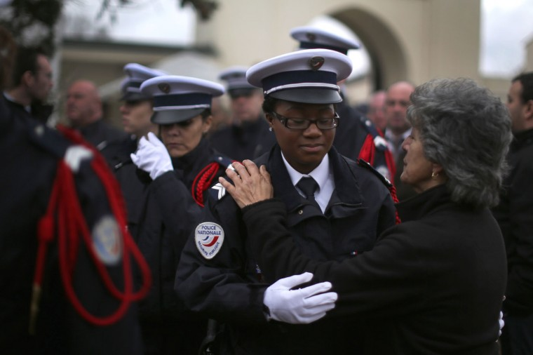 A woman embraces a police woman during the funeral of murdered police officer Ahmed Merabet at Bobigny Muslim cemetery on January 13, 2015 in Bobigny, France. The officers who were killed in last weeks' terrorist attacks were awarded a posthumous Legion dHonneur, in recognition of their bravery. The terrorist attacks began on Wednesday with the assault on the French satirical magazine Charlie Hebdo, killing 12, and ended on Friday with sieges at a printing company in Dammartin en Goele and a Kosher supermarket in Paris with four hostages and three suspects being killed. A fourth suspect, Hayat Boumeddiene, 26, escaped and is wanted in connection with the murder of a policewoman (Photo by Christopher Furlong/Getty Images)