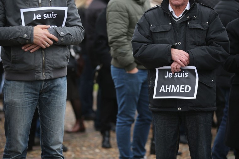 Mourners hold signs saying 'Je suis Ahmed' (I am Ahmed) during the funeral of murdered police officer Ahmed Merabet at Bobigny Muslim cemetery on January 13, 2015 in Bobigny, France. The officers who were killed in last weeks' terrorist attacks were awarded a posthumous Legion dHonneur, in recognition of their bravery. The terrorist attacks began on Wednesday with the assault on the French satirical magazine Charlie Hebdo, killing 12, and ended on Friday with sieges at a printing company in Dammartin en Goele and a Kosher supermarket in Paris with four hostages and three suspects being killed. A fourth suspect, Hayat Boumeddiene, 26, escaped and is wanted in connection with the murder of a policewoman (Photo by Christopher Furlong/Getty Images)
