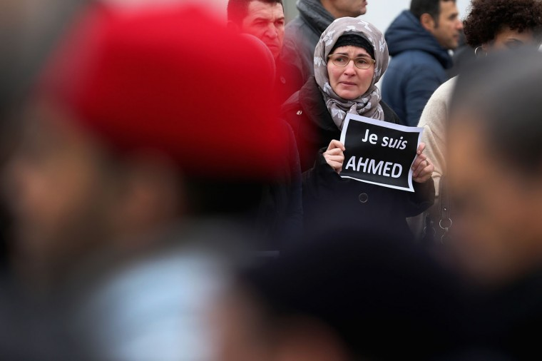 A mourner holds a sign saying 'Je suis Ahmed' (I am Ahmed) during the funeral of murdered police officer Ahmed Merabet takes place at Bobigny muslim cemetery on January 13, 2015 in Bobigny, France. The officers who were killed in last weeks' terrorist attacks were awarded a posthumous Legion dHonneur, in recognition of their bravery. The terrorist attacks began on Wednesday with the assault on the French satirical magazine Charlie Hebdo, killing 12, and ended on Friday with sieges at a printing company in Dammartin en Goele and a Kosher supermarket in Paris with four hostages and three suspects being killed. A fourth suspect, Hayat Boumeddiene, 26, escaped and is wanted in connection with the murder of a policewoman (Photo by Christopher Furlong/Getty Images)