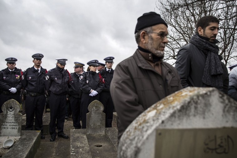 Police Officers line up at the funeral of murdered police officer Ahmed Merabet during the burial at a muslim cemetery on January 13, 2015 in Bobigny, France. All three police officers killed in last weeks attacks have been awarded a posthumous Legion d'Honneur, in recognition of their bravery. The terrorist attacks began on Wednesday with the assault on the French satirical magazine Charlie Hebdo, killing 12, and ended on Friday with sieges at a printing company in Dammartin en Goele and a Kosher supermarket in Paris with four hostages and three suspects being killed. A fourth suspect, Hayat Boumeddiene, 26, escaped and is wanted in connection with the murder of a policewoman. (Photo by Dan Kitwood/Getty Images)