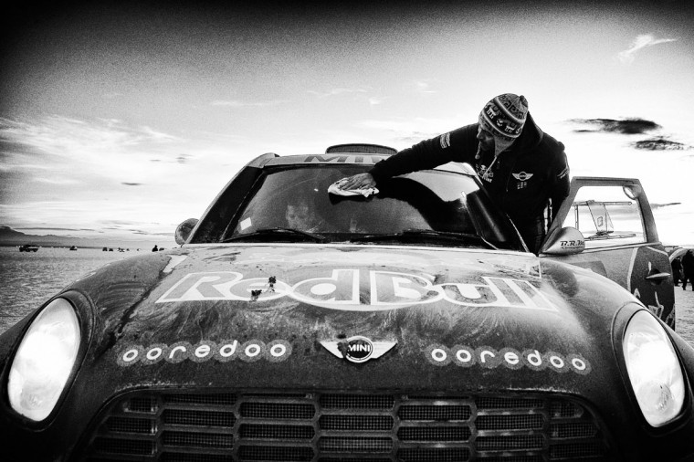 #301 Nasser Al Attiyah of Qatar cleans the windscreen and Mathieu Baumel of France waits in the car for the ALL4 Racing Mini Qatar Rally Team prior to starting day 8 of the Dakar Rally on the Salar de Uyuni or Uyuni Salt Flats on January 11, 2015 in Uyuni, Bolivia. (Photo by Dean Mouhtaropoulos/Getty Images)
