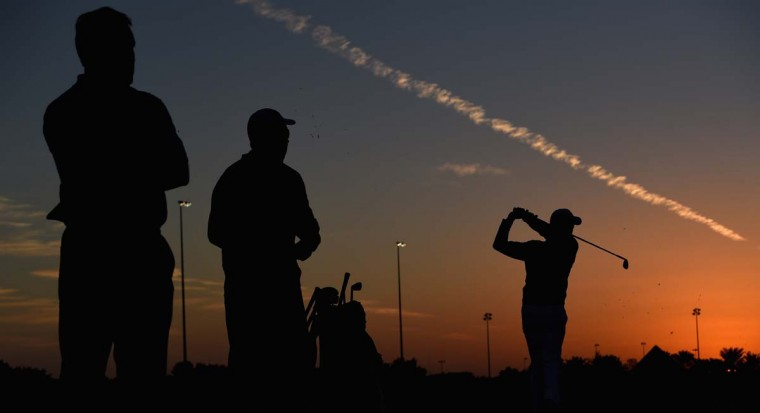 Rory McIlroy of Northern Ireland (R) is watched by his coach Michael Bannon (L) and caddie JP Fitzgerald on the practice range during the first round of the Abu Dhabi HSBC Golf Championship at the Abu Dhabi Golf Club on January 15, 2015 in Abu Dhabi, United Arab Emirates. (Photo by Ross Kinnaird/Getty Images)