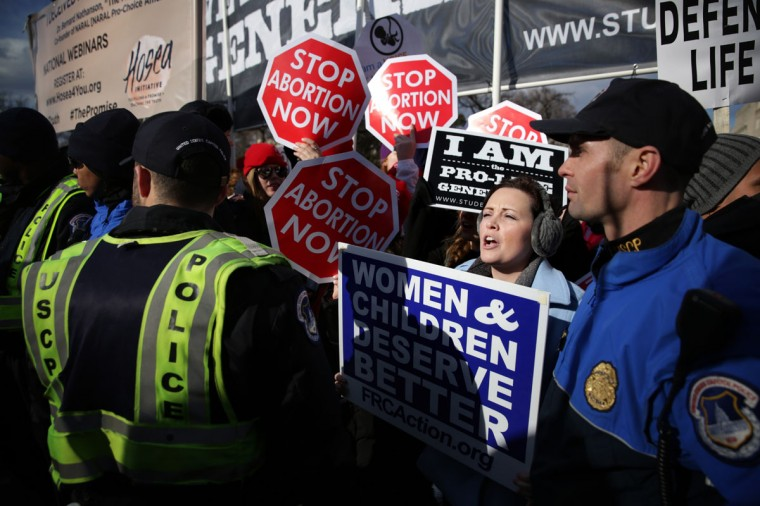 Pro-life activists hold signs as they watch the annual March for Life pass by in front of the U.S. Supreme Court January 22, 2015 in Washington, DC. (Photo by Alex Wong/Getty Images)