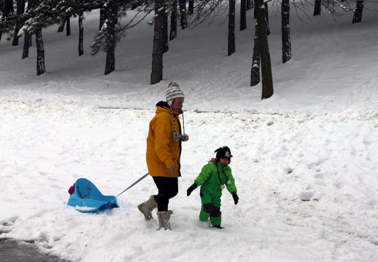 A mother and her child walk at a snow-covered park in Ankara, on January 6, 2015. (Adem Altan /AFP/Getty Images)