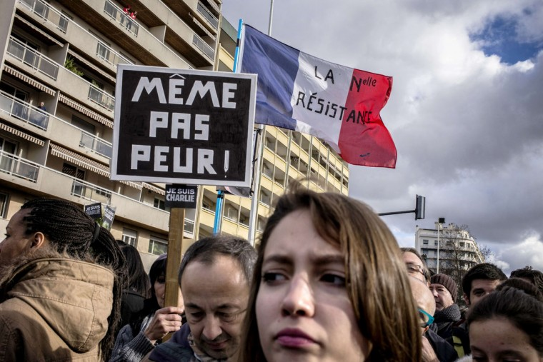 "People hold a placard reading ""Not even afraid"" and a French flag reading ""The new resistance"" take part in a Unity rally Marche Republicaine on January 11, 2015 in Lyon in tribute to the 17 victims of the three-day killing spree. The killings began on January 7 with an assault on the Charlie Hebdo satirical magazine in Paris that saw two brothers massacre 12 people including some of the country's best-known cartoonists and the storming of a Jewish supermarket on the eastern fringes of the capital which killed 4 local residents. (Jeff Pachoud/AFP/Getty Images)"