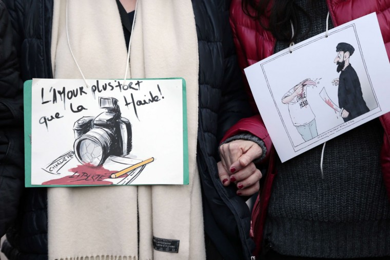"People hold cartoons, including one reading ""Love is stronger than hate"", during the Unity rally ""Marche Republicaine"" on January 11, 2015 in Paris in tribute to the 17 victims of a three-day killing spree by homegrown Islamists. The killings began on January 7 with an assault on the Charlie Hebdo satirical magazine in Paris that saw two brothers massacre 12 people including some of the country's best-known cartoonists, the killing of a policewoman and the storming of a Jewish supermarket on the eastern fringes of the capital which killed 4 local residents. (Joel Saget/AFP/Getty Images)"