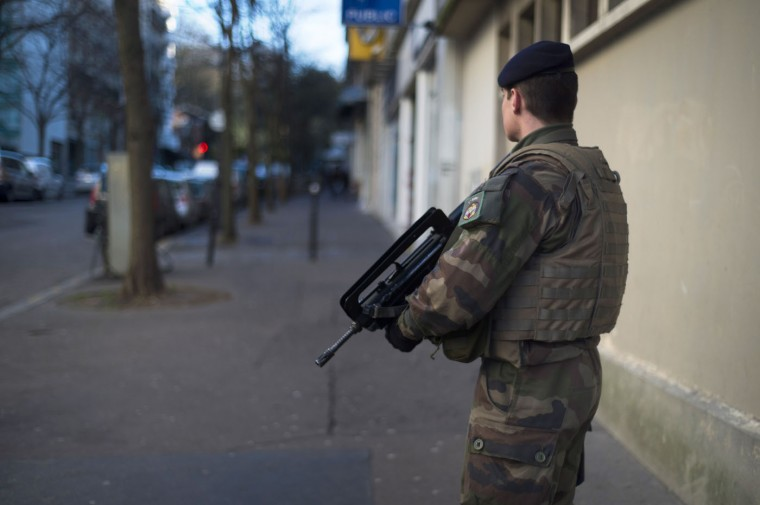 "A French soldier patrols on January 14, 2015 in Paris, after France announced an unprecedented deployment of thousands of troops and police to bolster security at ""sensitive"" sites following last week's jihadist attacks in Paris.The alert level in shell-shocked France remained at its highest possible as the interior minister announced the deployment of nearly 5,000 police to guard Jewish schools and places of worship. (Martin Bureau/AFP/Getty Images)"