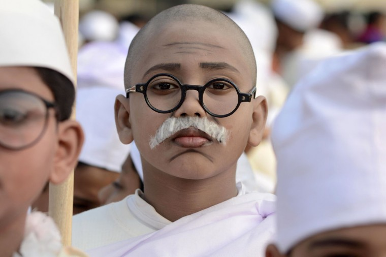 An Indian school child, dressed as Mahatma Gandhi, gestures during a rally on the birth anniversary of Indian nationalist, Netaji Subhas Chandra Bose at Agartala, the capital of northeastern state of Tripura on January 23, 2015. Prime Minister Narendra Modi paid tribute to freedom fighter Netaji Subhas Chandra Bose on his birth anniversary praising his bravery, courage and patriotic zeal. (AFP Photo/Arandam Dey)