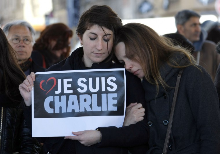 "People pay tribute to the victims of the satirical newspaper ""Charlie Hebdo"", in Marseille, southern France, Thursday, Jan. 8, 2015, a day after masked gunmen stormed the offices of a satirical newspaper and killed 12 people. French police hunted Thursday for two heavily armed men ó one with a terrorism conviction and a history in jihadi networks ó in the methodical killing of 12 people at a satirical newspaper that caricatured the Prophet Muhammad. Placard reads ""I am Charlie"". (AP Photo/Claude Paris)"