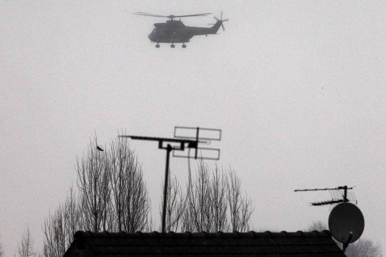 A police helicopter circles over Dammartin-en-Goele, northeast Paris, as part of an operation to seize two heavily armed suspects, Friday, Jan. 9, 2015. French security forces swarmed a small industrial town northeast of Paris Friday in an operation to capture a pair of heavily armed suspects in the deadly storming of a satirical newspaper. Shots were fired as the brothers stole a car in the early morning hours, said a French security official, who could not immediately confirm reports of hostages taken or deaths later in the day in the town of Dammartin-en-Goele, about 40 kilometers (25 miles) northeast of Paris. (AP Photo/Michel Spingler)