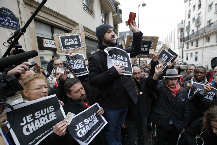 "Journalist hold up their press cards during a minute of silence outside the Charlie Hebdo newspaper in Paris, Thursday, Jan. 8, 2015, a day after masked gunmen stormed the offices of a satirical newspaper and killed 12 people. Protesters in some U.S. cities ó repeating the viral online slogan ""Je Suis Charlie"" or ""I Am Charlie"" demonstrated against the deadly terror attack on a Paris newspaper office, joining thousands around the world who took to the streets to rally against the killings. (AP Photo/Francois Mori)"