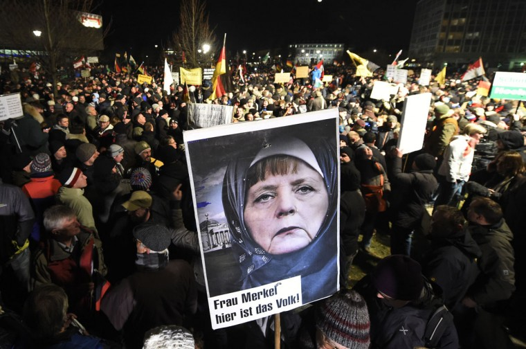 A protestor holds a poster showing German Chancellor Angela Merkel wearing a head scarf in front of the Reichtstags building with a crescent on top and the writing 'Mrs Merkel here is the people' during a rally of the group Patriotic Europeans against the Islamization of the West, or PEGIDA, in Dresden, Germany, Monday, Jan. 12, 2015. (AP Photo/Jens Meyer)