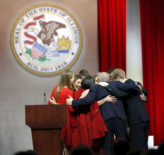 Illinois Gov. Bruce Rauner huddles with his family after being sworn in as Illinois' 42nd governor during ceremonies Monday, Jan. 12, 2015, in Springfield, Ill. (AP Photo/Charles Rex Arbogast)