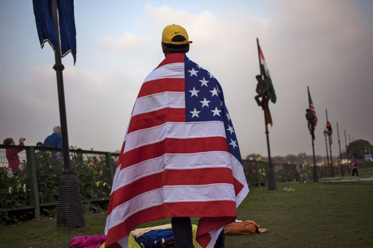 An Indian worker wears an American flag before it is hoisted up a flag pole in New Delhi, India, Friday, Jan. 23, 2015. India's Prime Minister Narendra Modi has invited U.S. President Barack Obama to be the first American president to attend Indiaís annual Republic Day festivities marked on Jan. 26. (AP Photo/Tsering Topgyal)