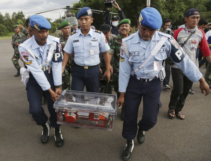 Indonesian air force personnel carry the flight data recorder of the ill-fated AirAsia Flight 8501 that crashed in the Java Sea, at the airport in Pangkalan Bun, Indonesia, Monday, Jan. 12, 2015. (AP Photo/Achmad Ibrahim)