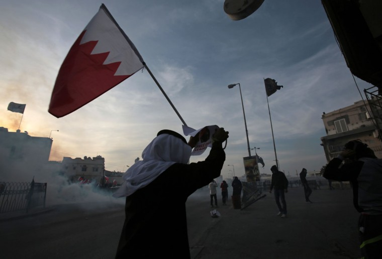 A Bahraini anti-government protester holds a national flag and a poster of jailed Shiite opposition leader Sheik Ali Salman during clashes with riot police firing tear gas in Bilad al Qadeem, Bahrain, Monday, Jan. 12, 2015. (AP Photo/Hasan Jamali)