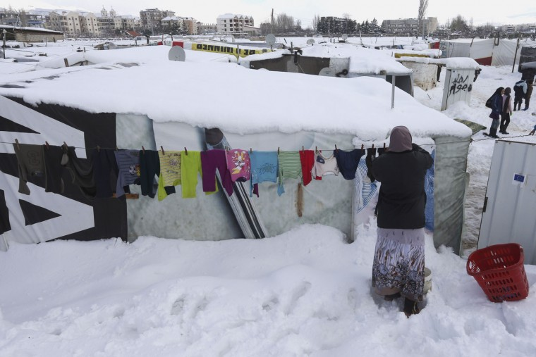 A Syrian woman hangs her laundry outside her tent covered by snow at a refugee camp in Zahleh town, Bekaa valley, east Lebanon, Thursday, Jan. 8, 2015. Snow fell in the Middle East as a powerful winter storm swept through the region, killing at least two Syrian refugees in Lebanon and forcing thousands of others who have fled their country civil war to huddle for warmth in refugee camps. (AP Photo/Hussein Malla)