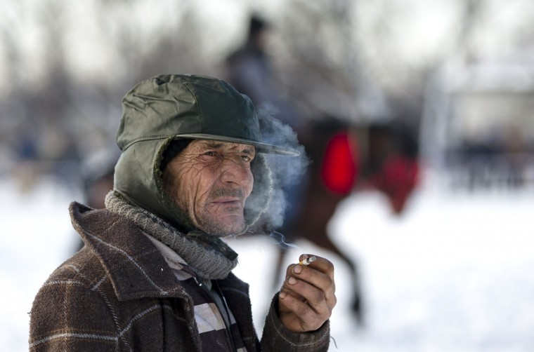 A man smokes waiting for the start of a traditional Epiphany celebration horse race in Pietrosani, Romania, Tuesday, Jan. 6, 2015. According to the local Epiphany traditions, following the religious service, villagers get their horses blessed with the Holy water then compete in a race. (AP Photo/Vadim Ghirda)