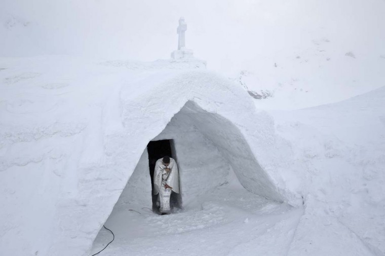 A Romanian priest exits a church built entirely from ice blocks cut from a frozen lake following a blessing religious service at the Balea Lac resort in the Fagaras mountains, Romania, Thursday, Jan. 29, 2015. The blessing was performed jointly by priests from all Christian denominations in Romania and the church, built at an altitude of over 2,000 meters, will host all types of religious events like weddings and baptizing ceremonies as long as the cold weather lasts.(AP Photo/Vadim Ghirda)