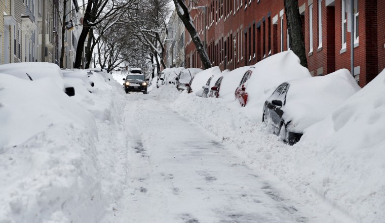 A car makes its way down a street filled with snowed-in vehicles in Boston's Charlestown section, Wednesday, Jan. 28, 2015 one day after a blizzard dumped about two feet of snow in the city. Residents of Massachusetts woke up Wednesday to cars buried in several feet of snow, and secondary roads that remain covered. (AP Photo/Elise Amendola)