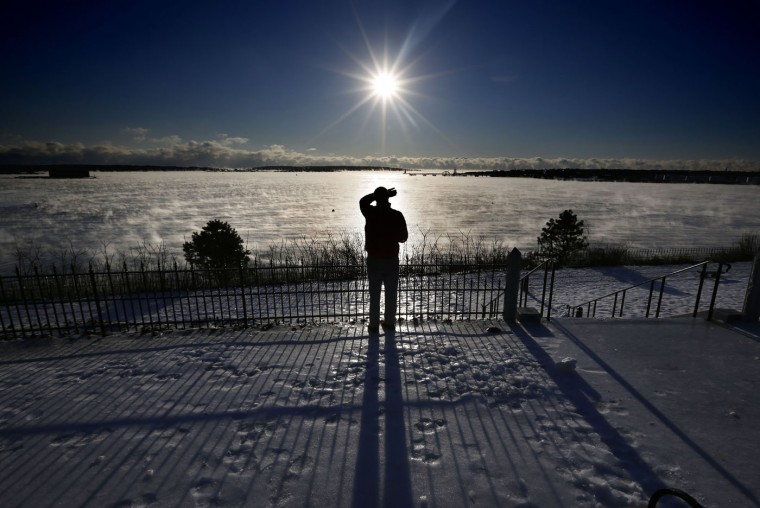 A man shields his eyes from the sun as he views the arctic sea smoke rising from Casco Bay, Thursday, Jan. 8, 2015, in Portland, Maine. Dangerously cold air has sent temperatures plummeting around the U.S. (AP Photo/Robert F. Bukaty)