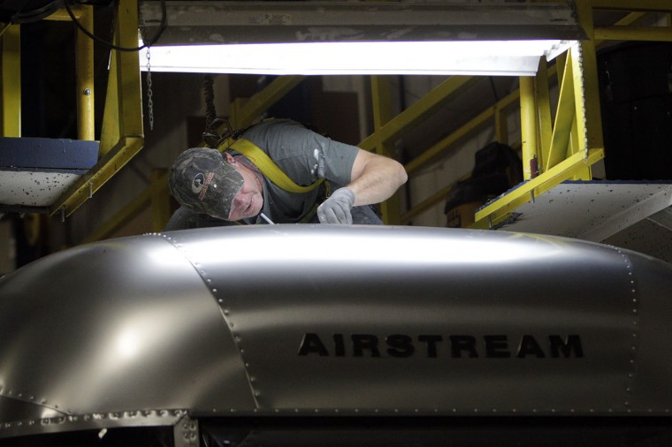 Jason Miley, of St. Marys, works on the roof of an Airstream travel trailer at the Airstream factory Wednesday, Oct. 22, 2014, in Jackson Center, Ohio. (AP Photo/Jay LaPrete)