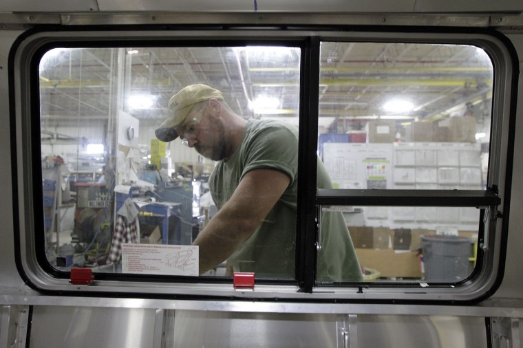 Shawn Stettler, of Anna, caulks around a window of an Airstream travel trailer at the Airstream factory Wednesday, Oct. 22, 2014, in Jackson Center, Ohio. (AP Photo/Jay LaPrete)