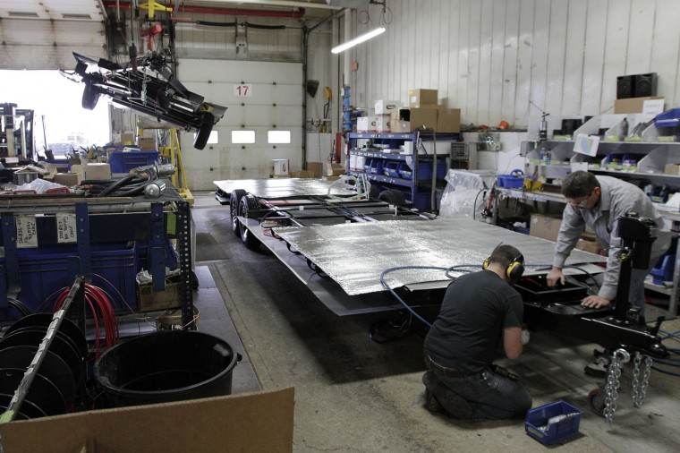 Employees attach the floor to the frame of an Airstream travel trailer at the Airstream factory Wednesday, Oct. 22, 2014, in Jackson Center, Ohio. (AP Photo/Jay LaPrete)
