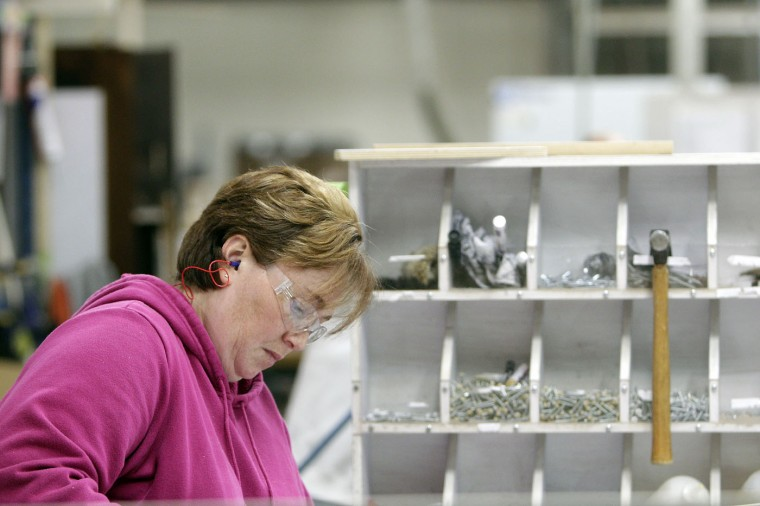 Tabatha Coil, of Bellefontaine, builds shelves for an Airstream travel trailer at the Airstream factory Wednesday, Oct. 22, 2014, in Jackson Center, Ohio. (AP Photo/Jay LaPrete)