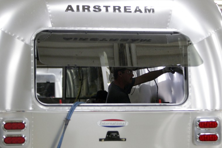 Employees work on an Airstream travel trailer at the Airstream factory Wednesday, Oct. 22, 2014, in Jackson Center, Ohio. (AP Photo/Jay LaPrete)