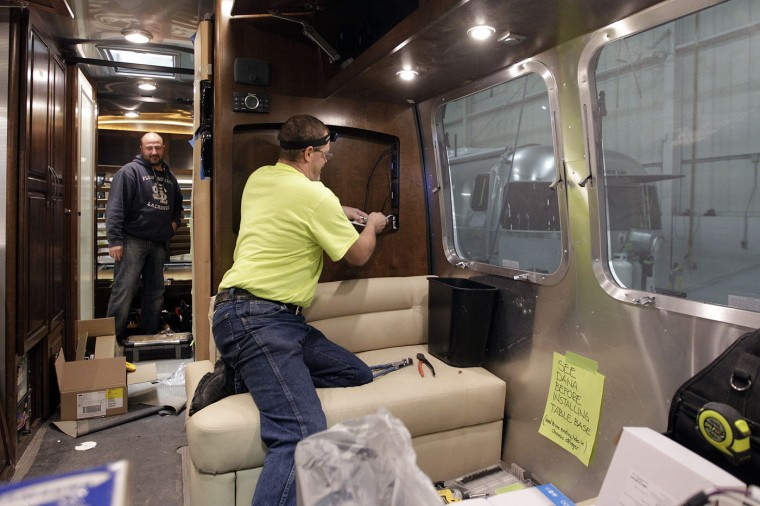 Employees install televisions in an Airstream travel trailer at the Airstream factory Wednesday, Oct. 22, 2014, in Jackson Center, Ohio. (AP Photo/Jay LaPrete)