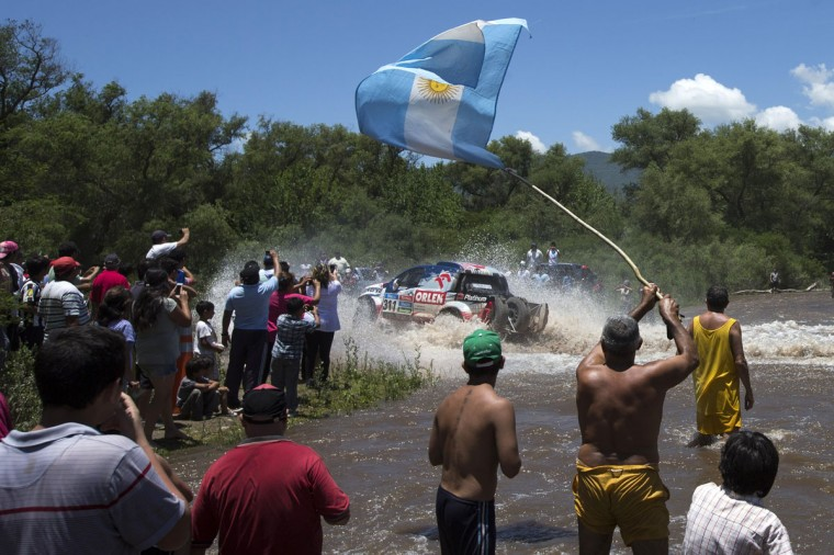 Spectators, one holding an Argentine national flag, watch as Toyota driver Marek Dabrowski and co-pilot Jacek Czachor, both of Poland, cross a river during the eleventh stage of the Dakar Rally 2015 between the cities of Salta and Termas de Rio Hondo, Argentina, Thursday, Jan. 15, 2015. The race returned to Argentina after passing through Bolivia and Chile and will finish on Jan. 17 in Buenos Aires. (AP Photo/Felipe Dana)
