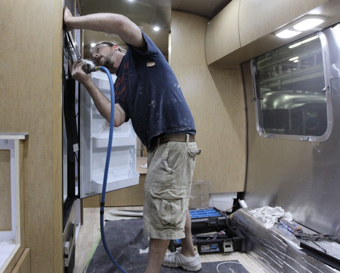 In this Oct. 22, 2014 photo, Matt Rainsburg, of Lima, installs a refrigerator in an Airstream travel trailer at the Airstream factory in Jackson Center, Ohio. Not only are the Airstream trailers still being built by hand at the same western Ohio site that has produced them for the past 60 years, but the company also can't roll them out of there fast enough to meet the demand these days. (AP Photo/Jay LaPrete)