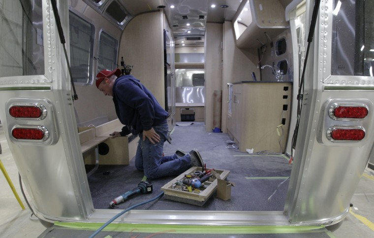 In this Oct. 22, 2014 photo, Rick March, of Jackson Center, installs a bench in an Airstream travel trailer at the Airstream factory in Jackson Center, Ohio. Not only are the Airstream trailers still being built by hand at the same western Ohio site that has produced them for the past 60 years, but the company also can't roll them out of there fast enough to meet the demand these days. (AP Photo/Jay LaPrete)