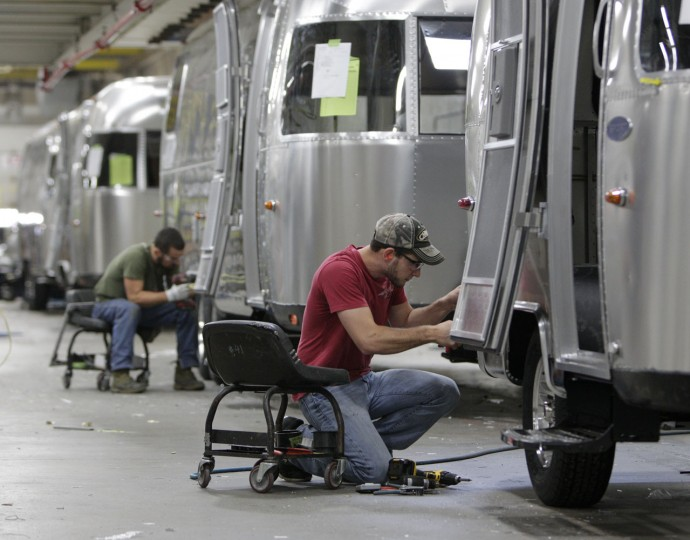 In this Oct. 22, 2014 photo, Jordan Peterson, of Bellefontaine, works on an Airstream travel trailer at the Airstream factory in Jackson Center, Ohio. Not only are the Airstream trailers still being built by hand at the same western Ohio site that has produced them for the past 60 years, but the company also can't roll them out of there fast enough to meet the demand these days. (AP Photo/Jay LaPrete)