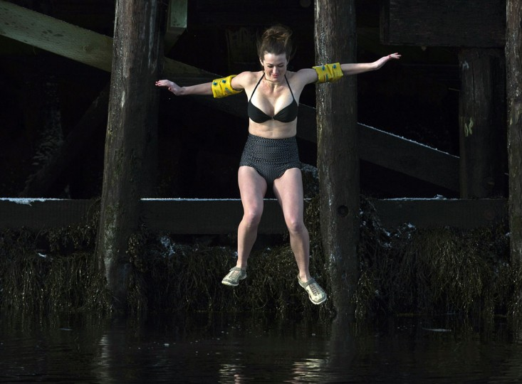 A woman wearing water wings inflatable arm floats welcomes the new year as she leaps from the government wharf into the frigid North Atlantic in the annual New Year's Day polar bear swim in Herring Cove, Nova Scotia, Canada, on Thursday, Jan. 1, 2015. (Andrew Vaughan/AP Photo/The Canadian Press)