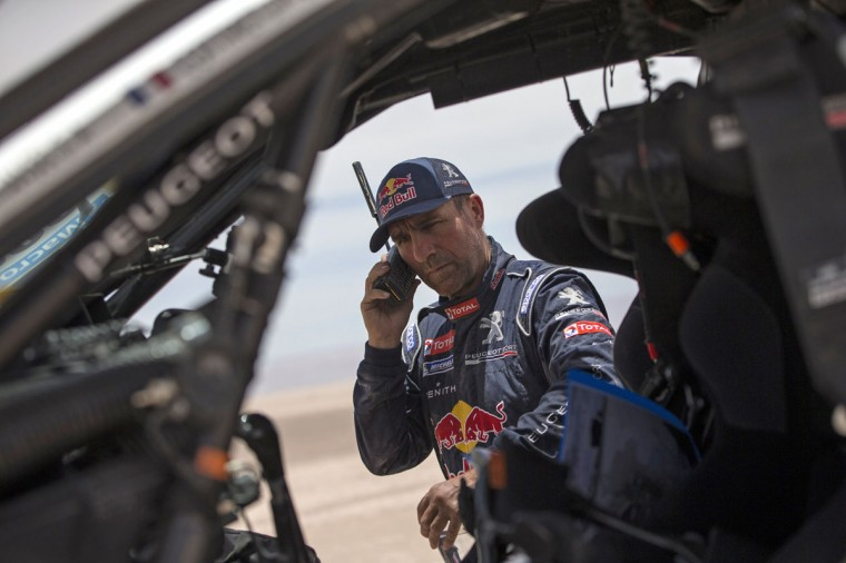 Peugeot driver Stephane Peterhansel, from France, talks on a sat phone after a mechanical problem during the ninth stage of the Dakar Rally between the cities of Iquique and Calama, Chile, Tuesday, Jan. 13, 2015. The race will finish on Jan. 17, passing through Bolivia and Chile before returning to Argentina where it started. (AP Photo/Felipe Dana)