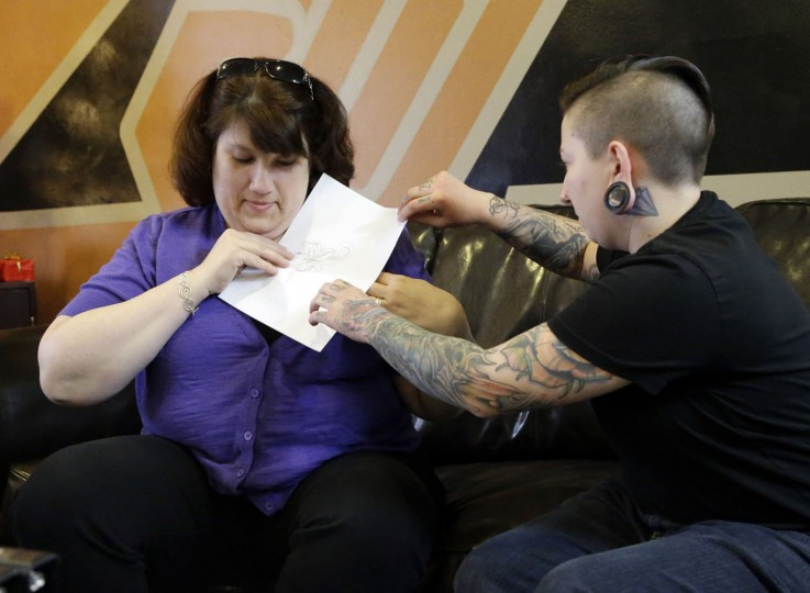 In this Wednesday, Dec. 17, 2014 photo, tattoo artist Ashley Neumann shows breast cancer survivor Mari Jankowski where her tattoo would be placed to cover her scar in West Allis, Wis. Jankowski wanted to cover her chemotherapy port scar on her upper left chest because she said people often mistook it for a hickey. (AP Photo/Morry Gash)