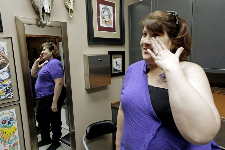 In this Wednesday, Dec. 17, 2014 photo, breast cancer survivor Mari Jankowski cries after seeing her new tattoo that covers a scar in West Allis, Wis. For women who have survived breast cancer, reconstructive surgery can be a first step toward looking like their old selves. The P.ink organization is helping some of those women with a step in their emotional healing - through tattoos to help conceal their scars. (AP Photo/Morry Gash)