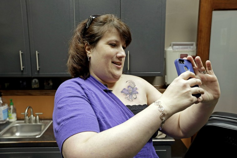 In this Wednesday, Dec. 17, 2014 photo, breast cancer survivor Mari Jankowski takes a photo of her new tattoo that covers a scar in West Allis, Wis. For women who have survived breast cancer, reconstructive surgery can be a first step toward looking like their old selves. The P.ink organization is helping some of those women with a step in their emotional healing - through tattoos to help conceal their scars. (AP Photo/Morry Gash)