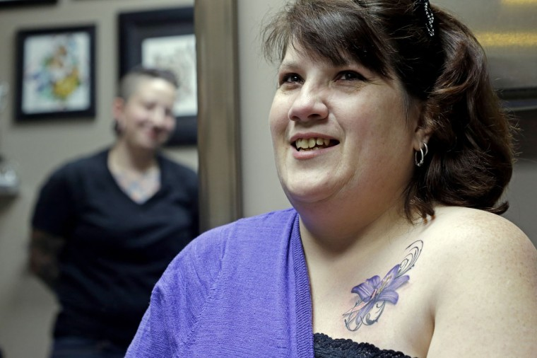 In this Wednesday, Dec. 17, 2014 photo, tattoo artist Ashley Neumann, left, watches as breast cancer survivor Mari Jankowski smiles as she talks about her new tattoo in West Allis, Wis. For women who have survived breast cancer, reconstructive surgery can be a first step toward looking like their old selves. The P.ink organization is helping some of those women with a step in their emotional healing - through tattoos to help conceal their scars. (AP Photo/Morry Gash)