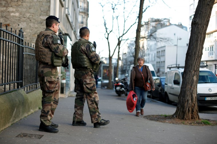"French soldiers secure the access to a Jewish school in Paris as part of the highest level of ""Vigipirate"" security plan after last week's attacks by Islamist militants, Wednesday, Jan. 14, 2015. France ordered 10,000 troops into the streets Monday to protect sensitive sites ó nearly half of them to guard Jewish schools ó as it hunted for accomplices to the Islamic militants who left 17 people dead as they terrorized the nation. (AP Photo/Thibault Camus)"